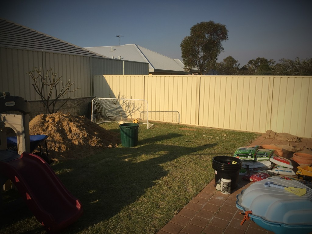 Image of backyard in afternoon with gardening supplies