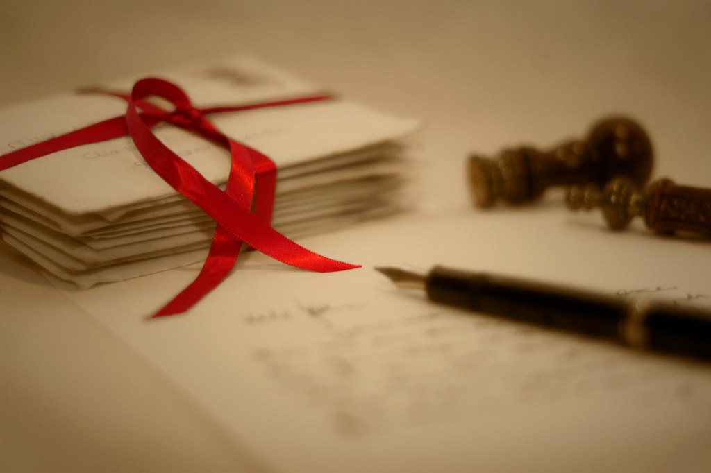 pile of letters tied with red ribbon and fountain pen on notepaper