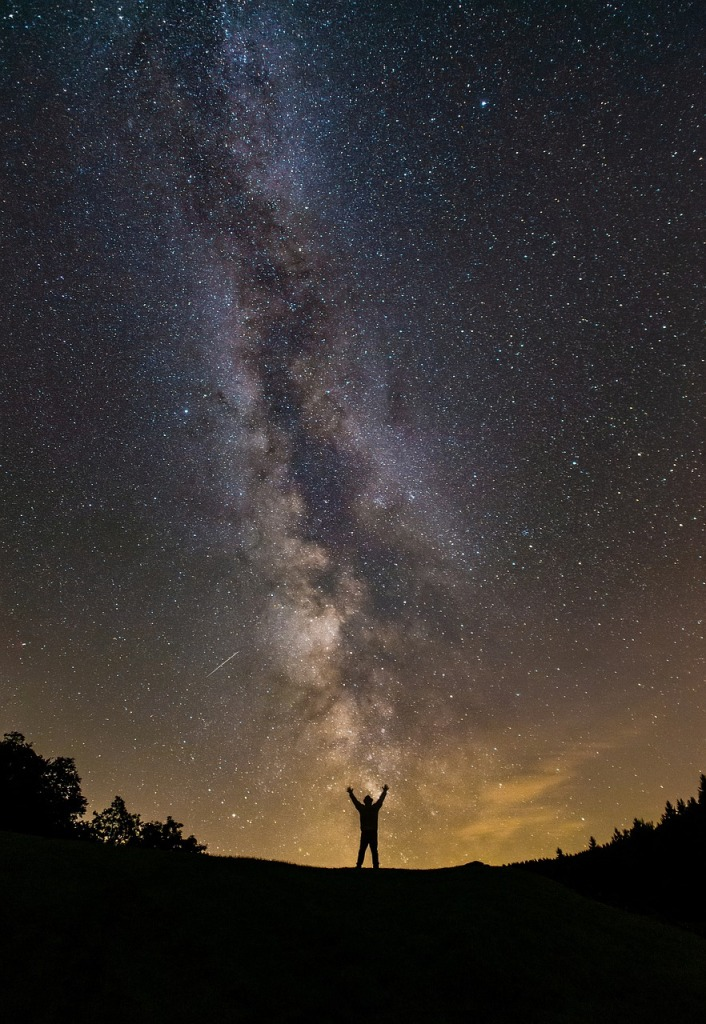 Man standing with arms raised beneath the milky way in the night sky