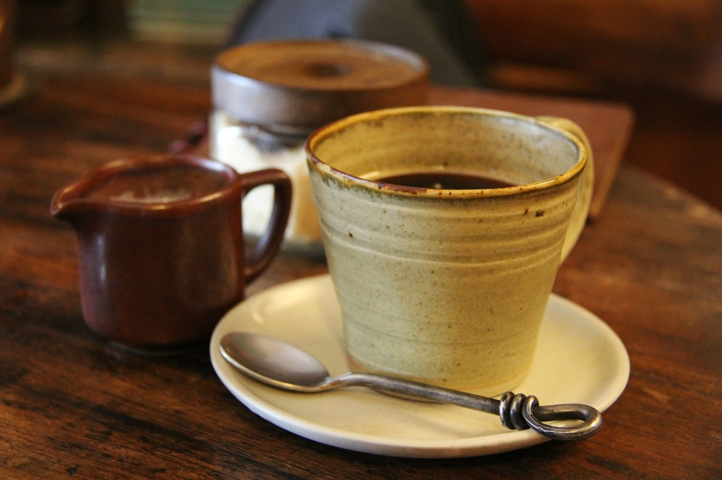 Two coffee and tea mugs with spoon, saucer and milk jug.