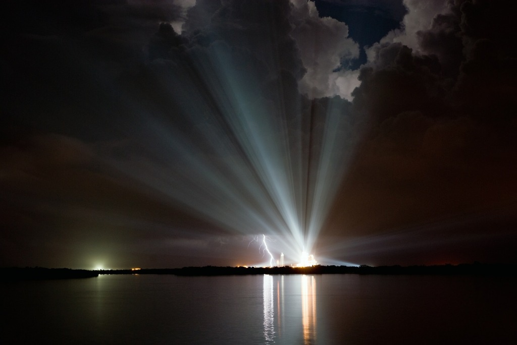 Space shuttle taking off with lightning and cloud reflections over the bay