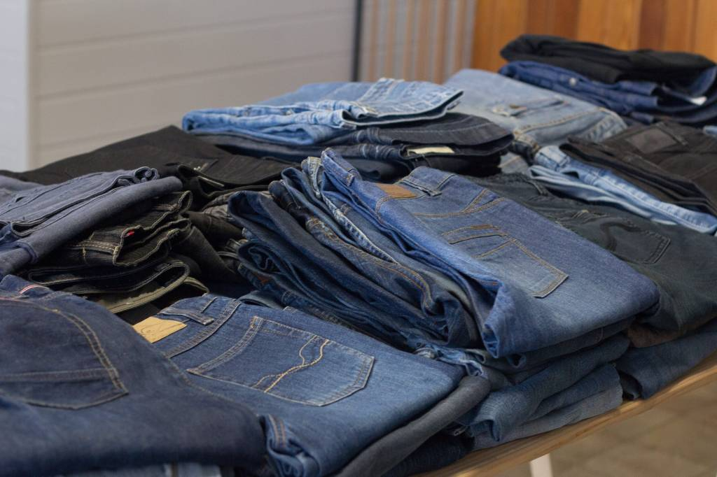 Folded jeans piled side by side on a tabletop.