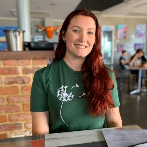 woman with long red hair and green tshirt in a cafe