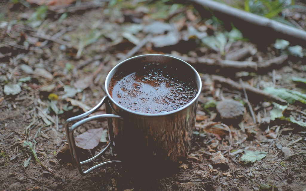 Filled brown mug on brown soil.
