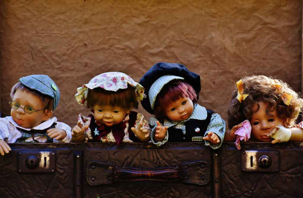 Four toy realistic dolls looking over a suitcase