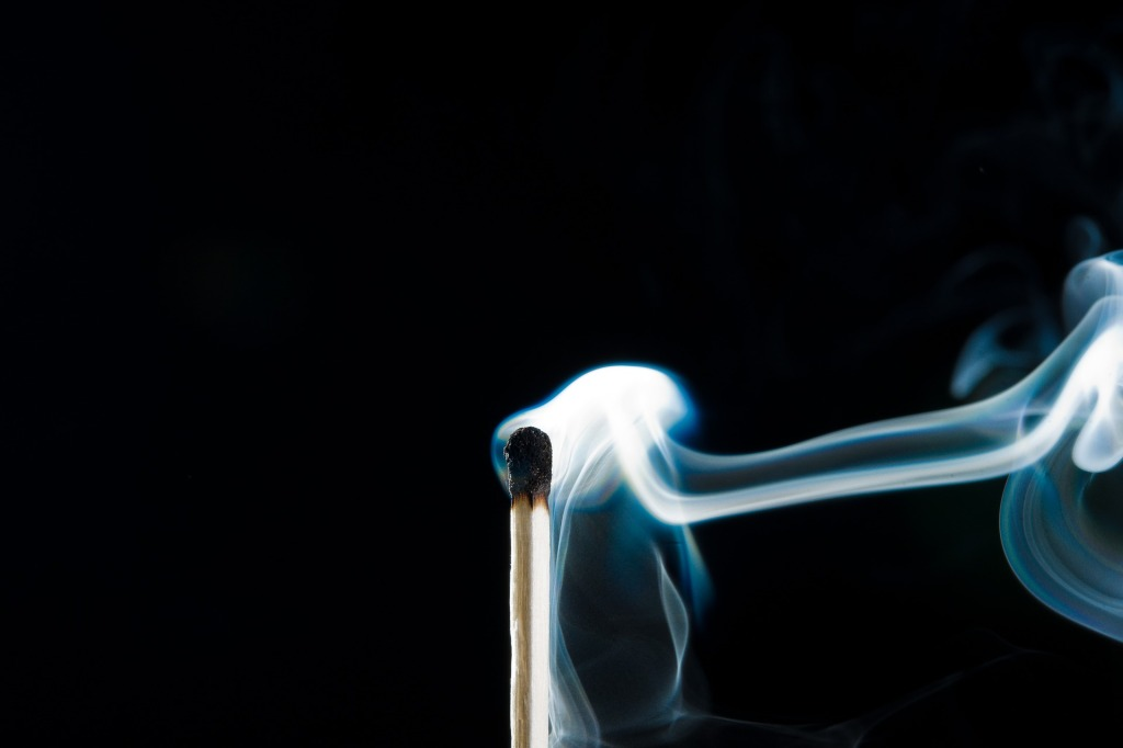 Wooden match with burnt black head and white smoke coming off, black background