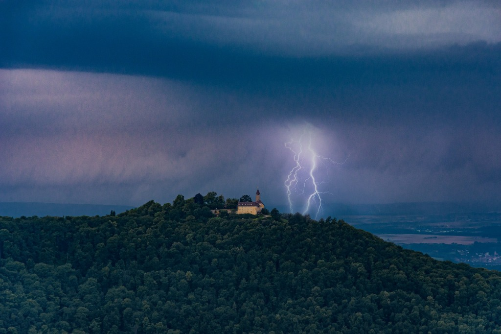 Castle on a wooded hill beneath dark clouds, lightning striking nearby.