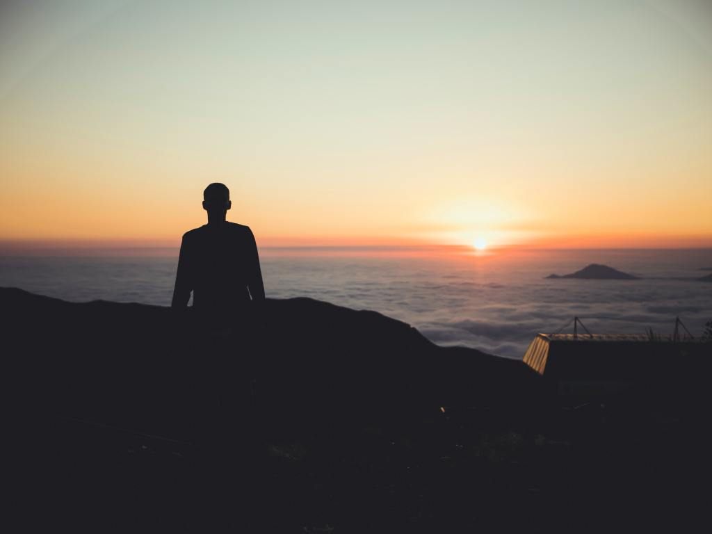 Silhouette of a human standing on a cliff looking out to sea, sun rising