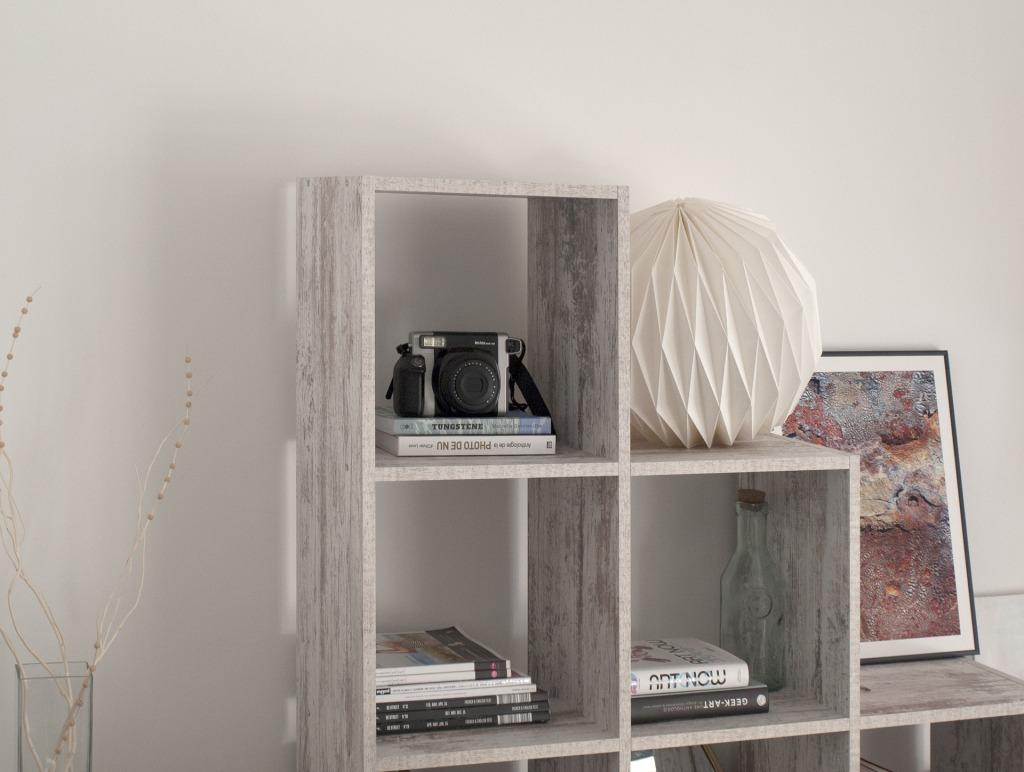 Open shelving unit with white origami globe, art books, art print, and polaroid camera