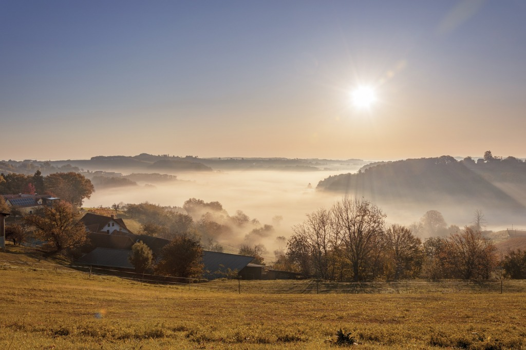 Golden field on a slope leading to pastoral house roofs, autumnal trees with bare branches or brown leaves, and fog over a valley with a bright sunrise