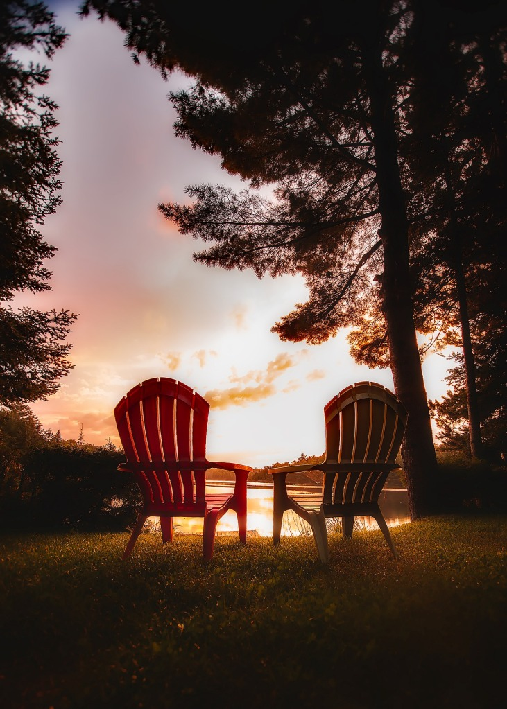 Two adirondack style chairs on grass, facing away towards a body of water, trees nearby, at sunset
