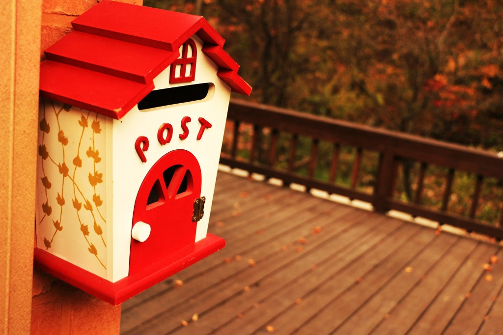 Post box on a wall; wooden verandah in background. Box looks like a small house with white walls, a red roof, red door, and POST on it.