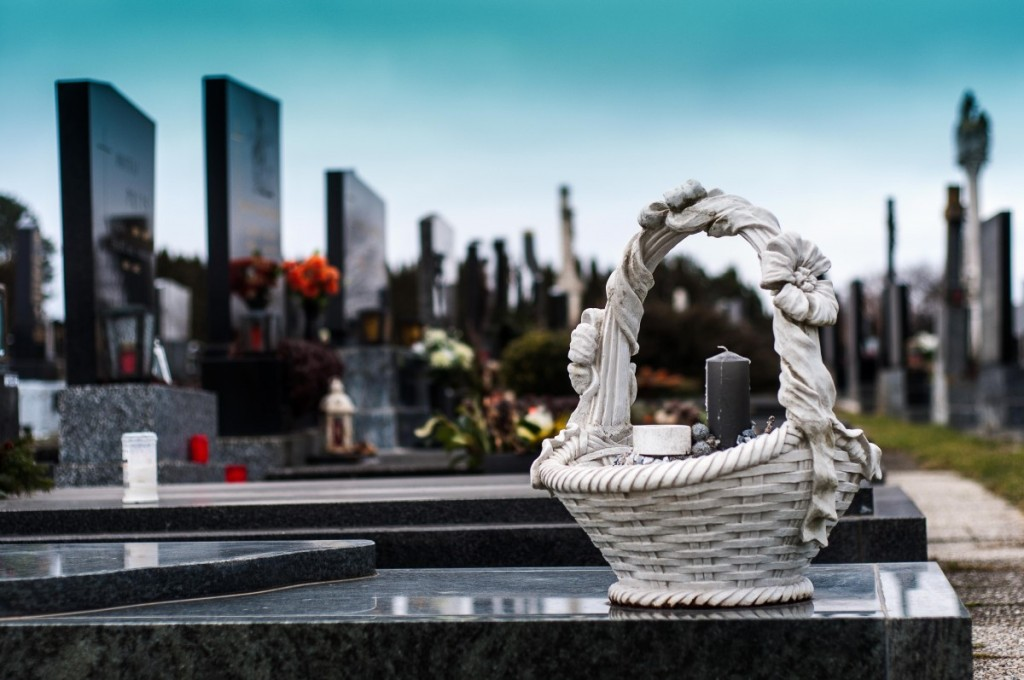 white woven basket with black candle and other indistinguishable gifts on a shiny black tombstone, other modern tombstones in background with gifts and flowers