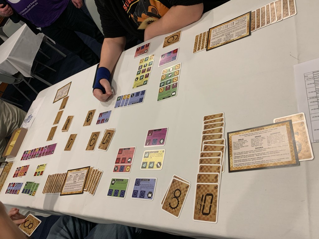 White table with a card game arrayed on it; cards are coloured with icons or have numbers and eras on a brown background. Two other players can be seen.