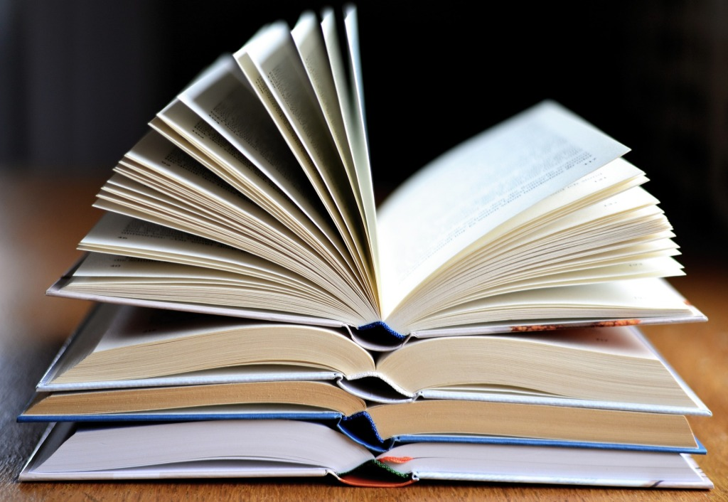 Four hardcover books stacked atop one another, each open to the approximate middle, on a brown tabletop