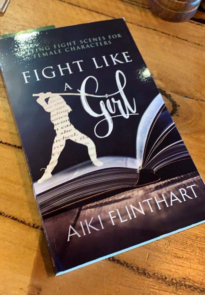 Fight Like A Girl by Aiki Flinthart book on a wooden table. The cover design has white font on dark blue and an open book on a wooden table/floorboard, with a paper cut-out of a woman's figure standing on the book holding a long, straight weapon above her head in a fighting stance.
