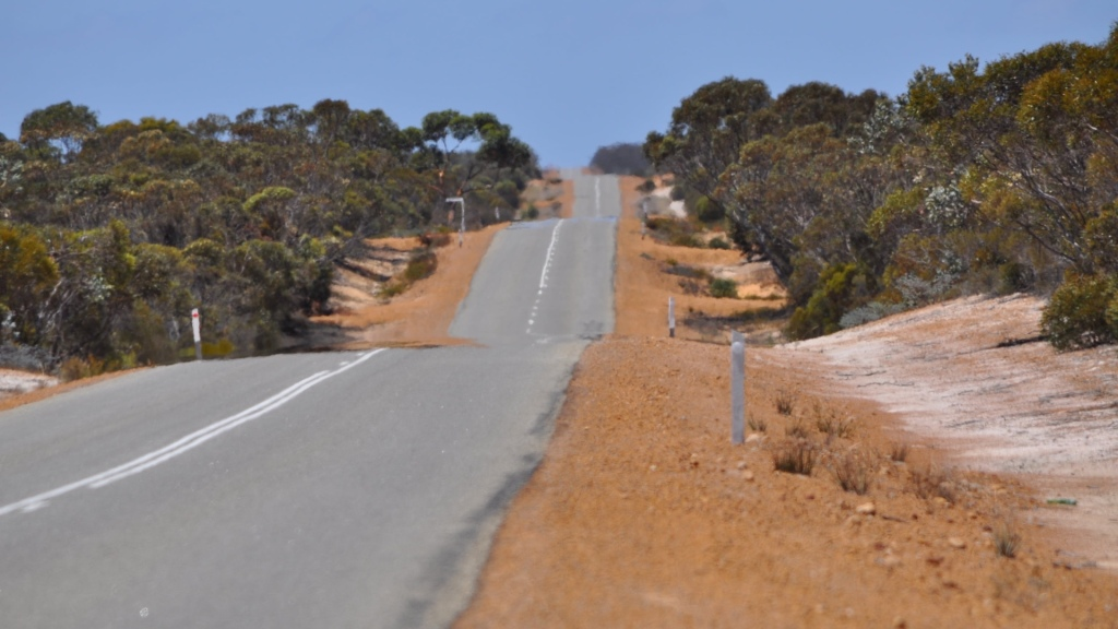 Asphalt road with white dividing line travelling from near to far distance over small hills, red and white dirt to each side, green Australian bush plants, pale blue sky