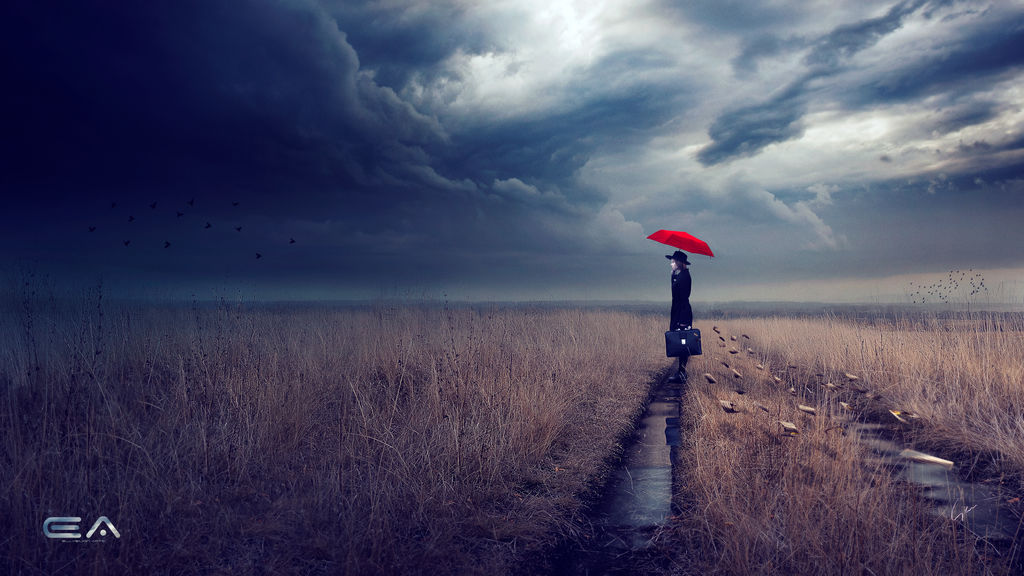 Thundercloud sky over a field of dead grass through which runs a track filled with water. A person stands on the track with a briefcase, black coat, black hat, and red umbrella