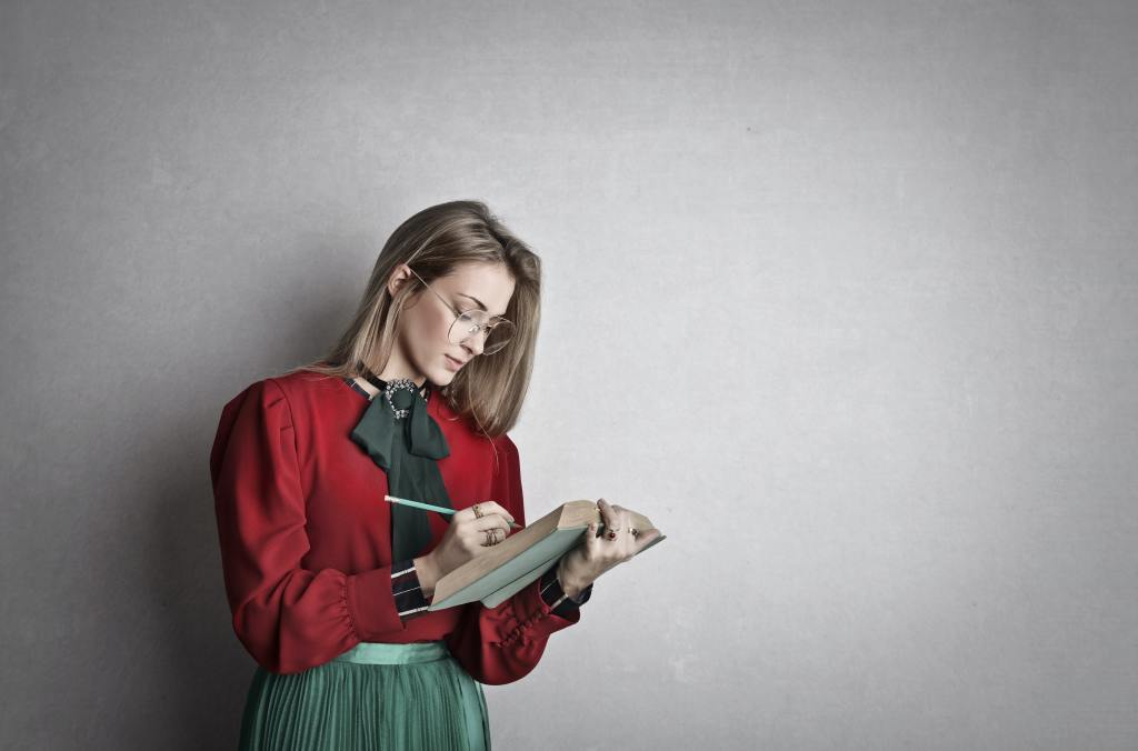 Smart adult female student reading a book while standing, holding a pencil in one hand poised to write on the page.